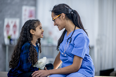 Nursing student talking to young female patient