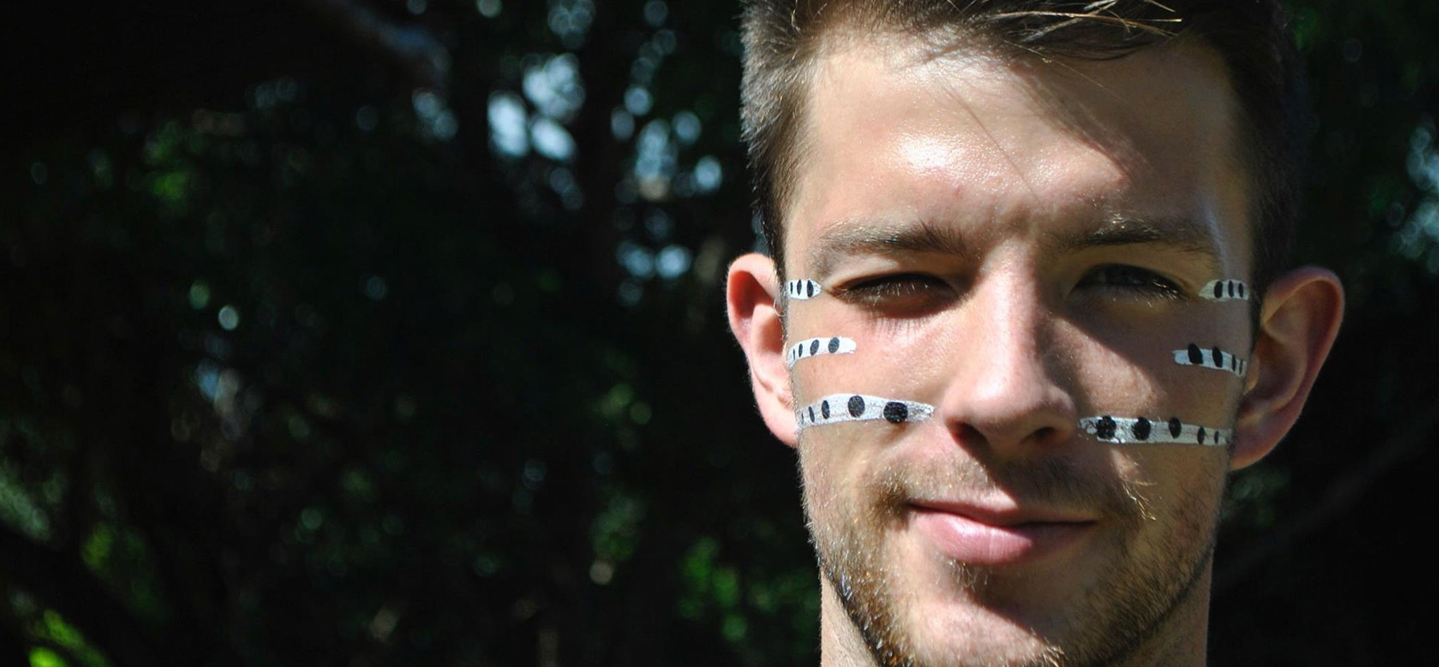 A male student wears traditional face paint during a travel course to Australia