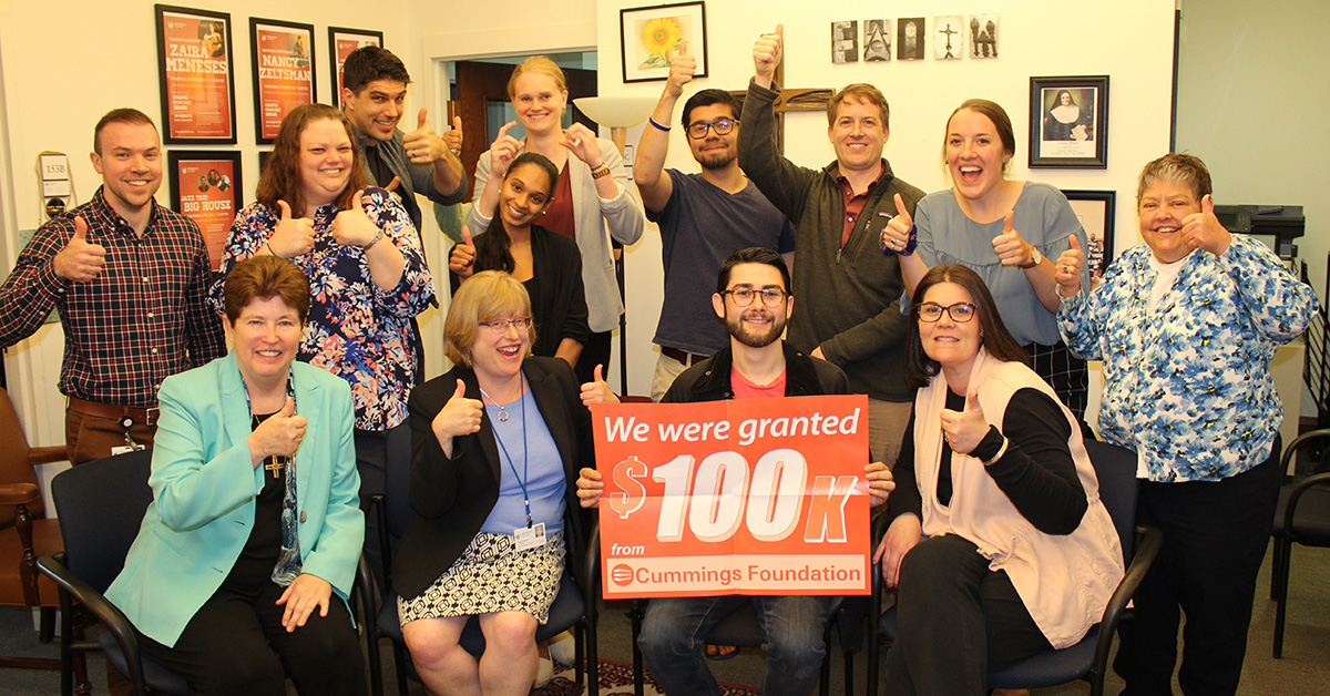 "Students, faculty and staff of Emmanuel in the College's Mission and Minsitry Office presenting a red sign that reads ""we were granted 100k from Cummings Foundation"